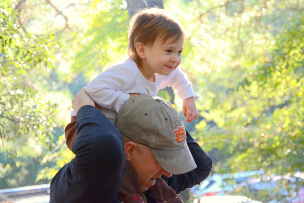 Happy child on dad's shoulders in sunlight