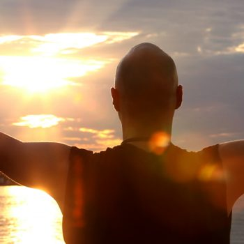 man practicing mindfulness with arms outstretched at sunrise