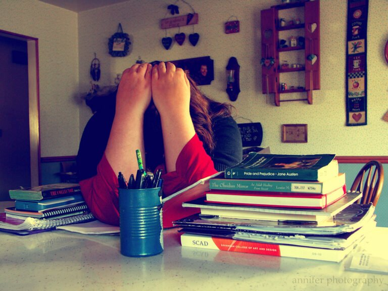 Stressed student with head in hands by pile of textbooks