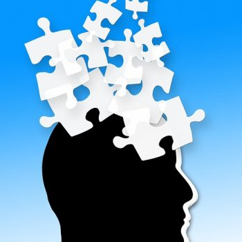 Head in silhouette with overlapping puzzle pieces