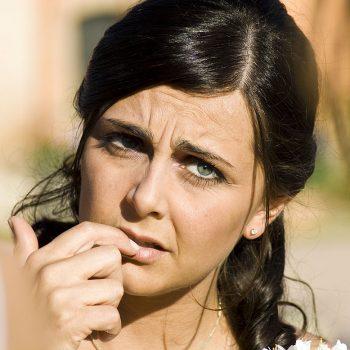 Anxious woman's face biting nail