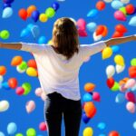 Woman facing blue sky full of colorful baloons - expressing positive outlook arms stretched wide