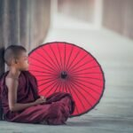 Meditating Boy with Red Umbrella