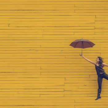 Happy woman holding umbrella leping in front of yellow wall