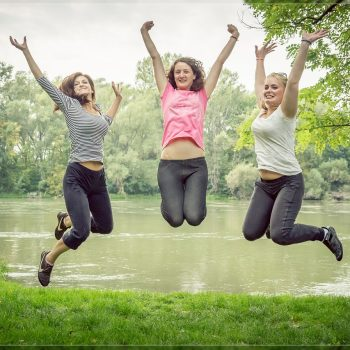 3 happy girls jumping together by pond