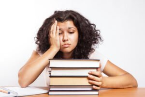 Worried college student leaning on hand in front of textbooks