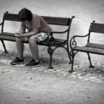 Sad Teen sitting alone on bench