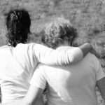 Two women hugging side by side from back