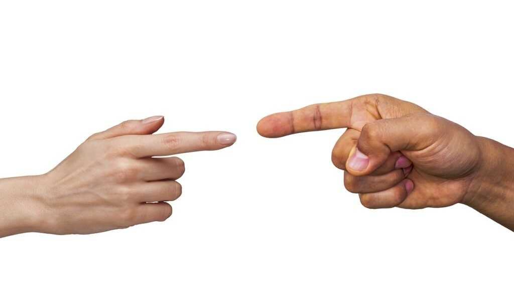 Man and woman's hands pointing fingers at each other