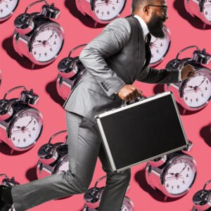 Businessman running with briefcase in front of alarm clocks