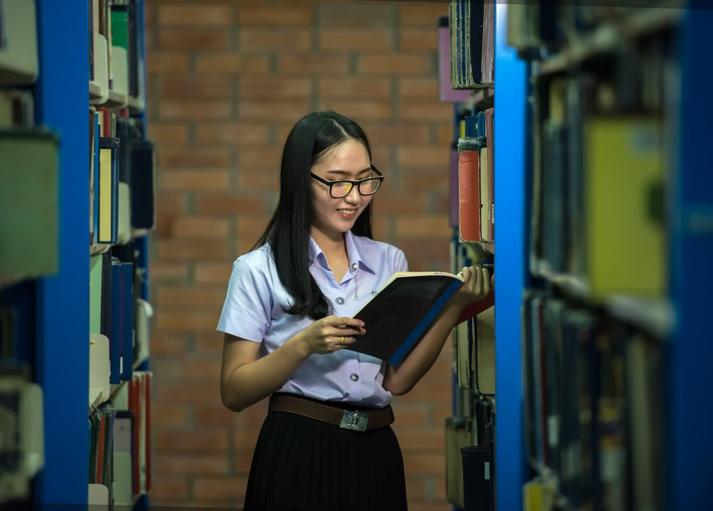 College student perusing books in library stack